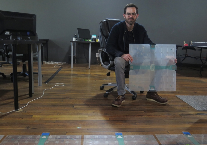 In this photo taken Dec. 5, 2017, Scanalytics co-founder and CEO Joe Scanlin holds a smart floor sensor his company creates that track people's movements in Milwaukee. The sensors are among the tools retailers are using to gain insights on consumer habits. (AP Photo/Ivan Moreno)
