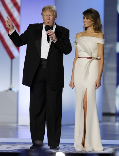 "FILE - In this Jan. 20, 2017 file photo, President Donald Trump with first lady Melania arrive at the Freedom Ball in Washington at the Washington Convention Center during the 58th presidential inauguration. Slovenian-born Melania Trump has been unafraid to go against her husband's ""America First"" agenda, and stay true to her roots, if there's a message to be taken from her bold, foreign-flavored first lady wardrobe in 2017. (AP Photo/Mark Tenally)"