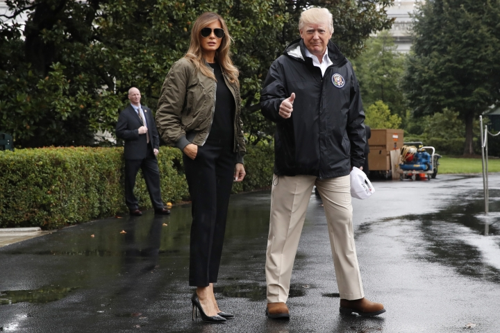 """FILE - In this Aug. 29, 2017 file photo, President Donald Trump, accompanied by first lady Melania Trump, gives a thumbs-up as they walk to Marine One on the South Lawn of the White House in Washington, for a short trip to Andrews Air Force Base, Md., then onto Texas to survey the response to Hurricane Harvey. Slovenian-born Melania Trump has been unafraid to go against her husband's """"America First"""" agenda, and stay true to her roots, if there's a message to be taken from her bold, foreign-flavored first lady wardrobe in 2017. (AP Photo/Jacquelyn Martin)"""