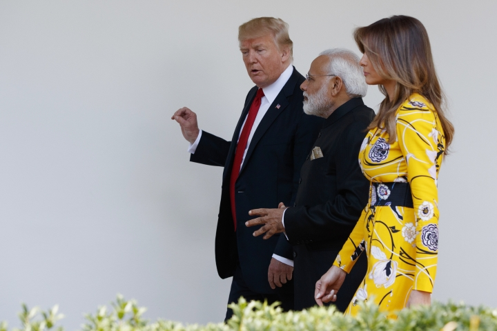 "FILE - In this June 26, 2017 file photo, President Donald Trump and first lady Melania Trump walk with Indian Prime Minister Narendra Modi at the White House in Washington. Melania Trump has been unafraid to go against her husband's ""America First"" agenda, and stay true to her roots, if there's a message to be taken from her bold, foreign-flavored first lady wardrobe in 2017. She is wearing a yellow floral Pucci dress. (AP Photo/Evan Vucci)"