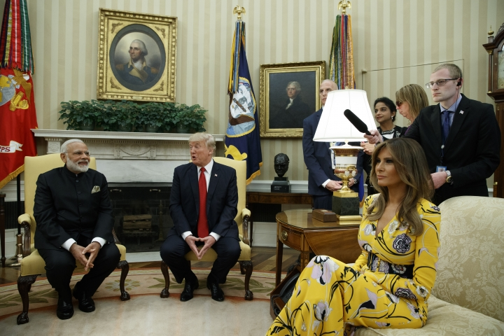 FILE - In this June 26, 2017 file photo, President Donald Trump, accompanied by first lady Melania Trump, meets with Indian Prime Minister Narendra Modi in the Oval Office of the White House in Washington. Melania Trump is wearing a yellow floral Pucci dress. (AP Photo/Evan Vucci)