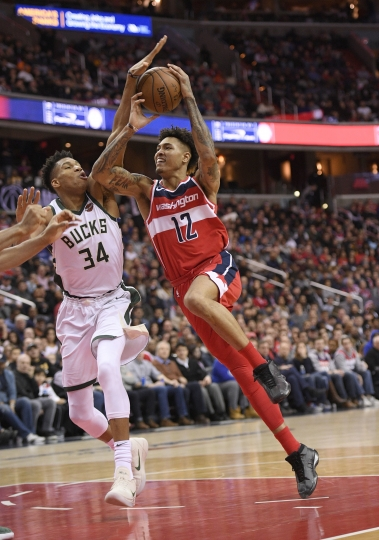 Washington Wizards forward Kelly Oubre Jr. (12) is fouled by Milwaukee Bucks forward Giannis Antetokounmpo (34), of Greece, during the second half of an NBA basketball game, Monday, Jan. 15, 2018, in Washington. The Bucks won 104-95. (AP Photo/Nick Wass)
