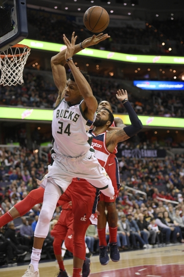 Milwaukee Bucks forward Giannis Antetokounmpo (34), of Greece, is fouled by Washington Wizards forward Markieff Morris, second from left, during the first half of an NBA basketball game, Monday, Jan. 15, 2018, in Washington. (AP Photo/Nick Wass)
