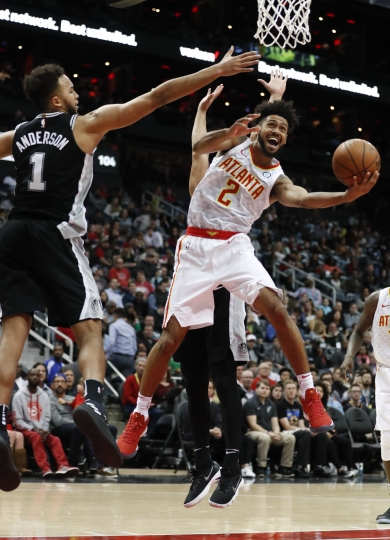 Atlanta Hawks guard Tyler Dorsey (2) scores against San Antonio Spurs forward Kyle Anderson (1) in the second half of an NBA basketball game Monday, Jan. 15, 2018, in Atlanta. The Hawks won 102-99. (AP Photo/John Bazemore)