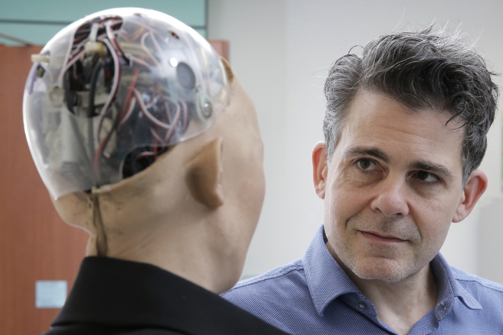 "In this Sept. 28, 2017, photo, David Hanson, the founder of Hanson Robotics, talks with his company's flagship robot Sophia, a lifelike robot powered by artificial intelligence in Hong Kong. Sophia is a creation of the Hong Kong-based startup working on bringing humanoid robots to the marketplace. Hanson envisions a future in which AI-powered robots evolve to become ""super-intelligent genius machines"" that can help solve mankind's most challenging problems. (AP Photo/Kin Cheung)"