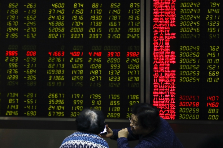 Women chat as they monitor stock prices at a brokerage house in Beijing, Tuesday, Jan. 16, 2018. Asian stock markets have risen following a holiday for U.S. markets as investors look ahead to American corporate earnings reports. (AP Photo/Andy Wong)
