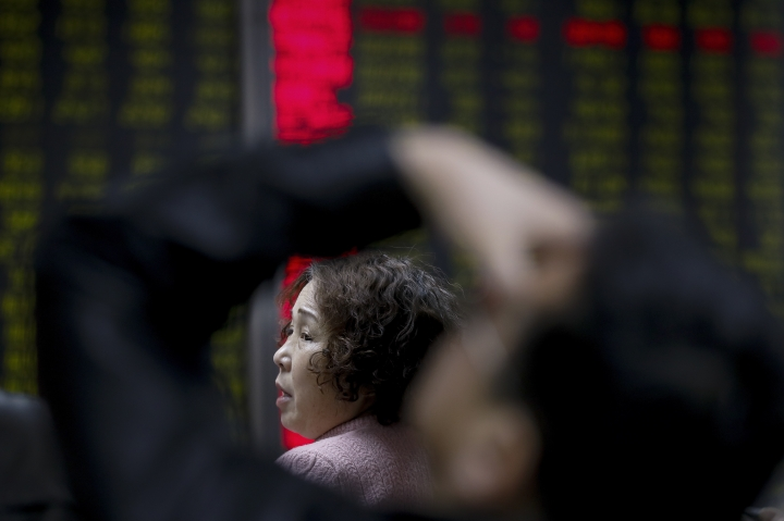 A woman chats with her friend as they monitor stock prices at a brokerage house in Beijing, Tuesday, Jan. 16, 2018. Asian stock markets have risen following a holiday for U.S. markets as investors look ahead to American corporate earnings reports. (AP Photo/Andy Wong)