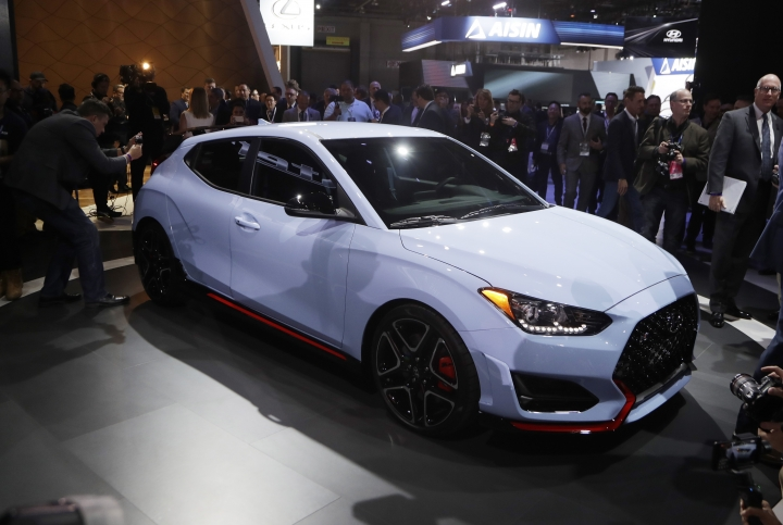Journalists look over the 2019 Veloster N model during the North American International Auto Show, Monday, Jan. 15, 2018, in Detroit. (AP Photo/Carlos Osorio)
