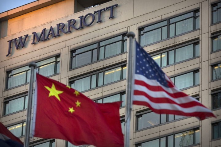 FILE - In this Jan. 11, 2018, file photo, Chinese and American flags fly outside of a JW Marriott hotel in Beijing. Politics weighs more heavily on foreign companies in China than it has in nearly three decades, as companies face pressure on many sides from Chinese President Xi Jinping's more nationalistic stance and twin campaigns to tighten the ruling Communist Party's political control and have it play a more direct role in business. (AP Photo/Mark Schiefelbein, File)