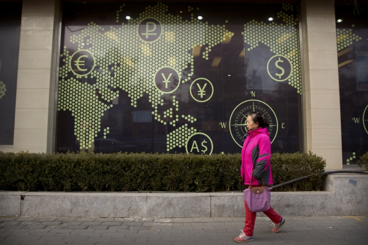 A woman walks past a display showing symbols for world currencies on the exterior of a bank in Beijing, Thursday, Jan. 18, 2018. Financial regulators in China say cross-border capital flows hit a turning point in 2017 as foreign currency reserve levels stabilized after two years of declines. (AP Photo/Mark Schiefelbein)