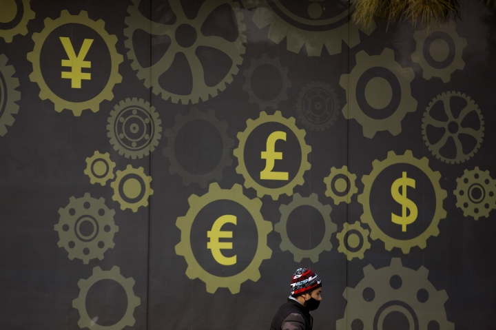 A deliveryman wearing a face mask walks past a display showing symbols for world currencies on the exterior of a bank in Beijing, Thursday, Jan. 18, 2018. Financial regulators in China say cross-border capital flows hit a turning point in 2017 as foreign currency reserve levels stabilized after two years of declines. (AP Photo/Mark Schiefelbein)