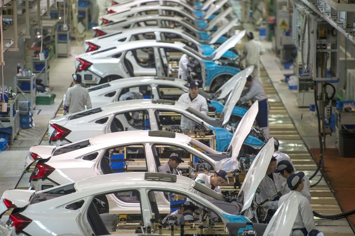 In this Feb. 6, 2017 photo, workers assemble Honda Civics on an assembly line at a Dongfeng Honda automotive plant in Wuhan in central China's Hubei province. China's economy expanded at a 6.9 percent pace in 2017, faster than expected and the first annual increase in seven years, the government reported Thursday, Jan. 18, 2018. (Chinatopix via AP)