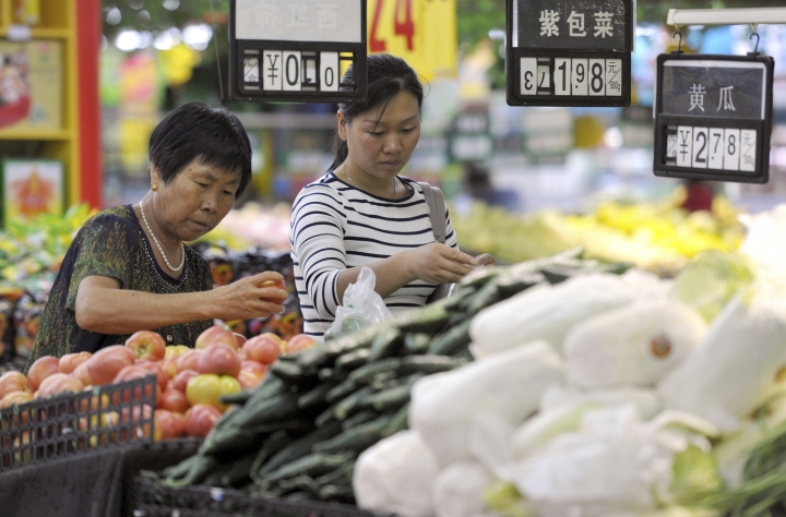 In this Sept. 9, 2017 photo, women shop for produce at a supermarket in Fuyang in central China's Anhui province. China's economy expanded at a 6.9 percent pace in 2017, faster than expected and the first annual increase in seven years, the government reported Thursday, Jan. 18, 2018. (Chinatopix via AP)