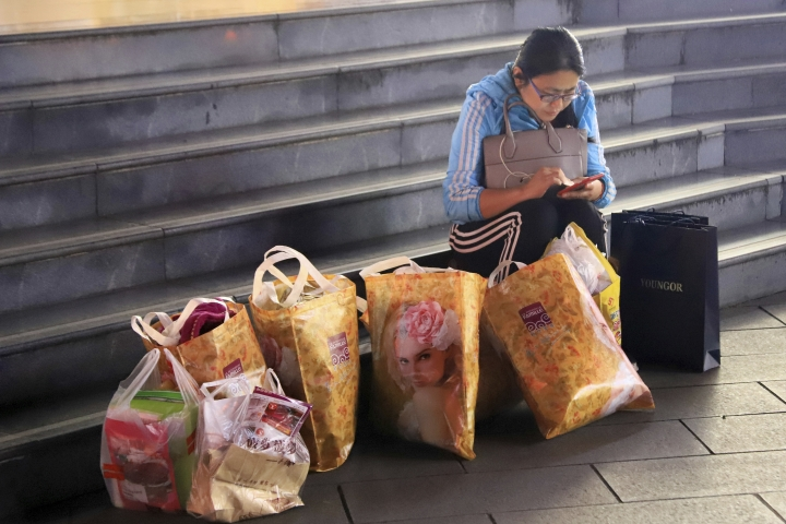 In this Nov. 11, 2017 photo, a woman uses her smartphone as she sits with her shopping bags on the steps outside of a store in Ningbo in eastern China's Zhejiang province. China's economy expanded at a 6.9 percent pace in 2017, faster than expected and the first annual increase in seven years, the government reported Thursday, Jan. 18, 2018. (Chinatopix via AP)