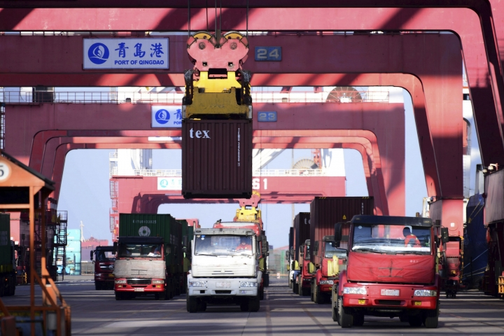 In this Jan. 12, 2018 photo, trucks move shipping containers at a port in Qingdao in eastern China's Shandong province. China's economy expanded at a 6.9 percent pace in 2017, faster than expected and the first annual increase in seven years, the government reported Thursday, Jan. 18, 2017. (Chinatopix via AP)