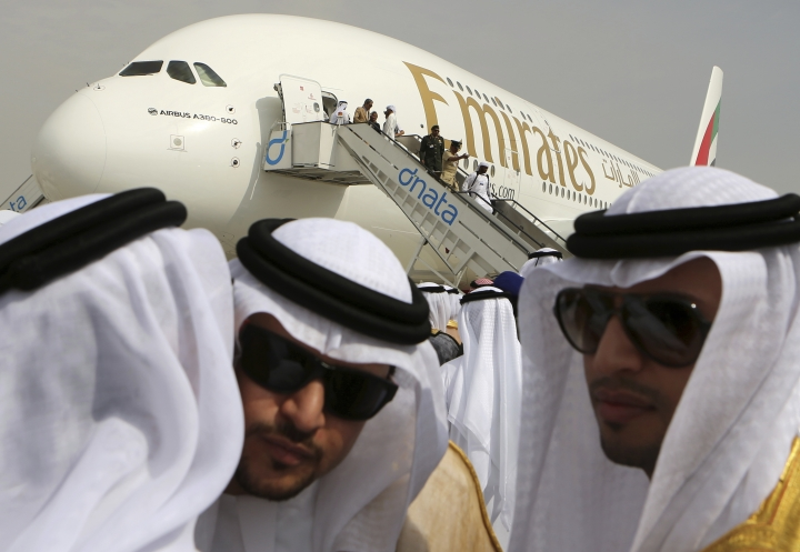 FILE - In this Nov. 17, 2013 file photo, Emirati officials greet each other in front of an Emirates Airbus A380 on display during the opening day of the Dubai Airshow in Dubai, United Arab Emirates. Emirates airline said in a statement Thursday, Jan. 18, 2018, that they are purchasing 20 A380 aircraft with the option for 16 more in a deal worth $16 billion, throwing a lifeline to the European-made double-decker jumbo jets. (AP Photo/Kamran Jebreili, File)