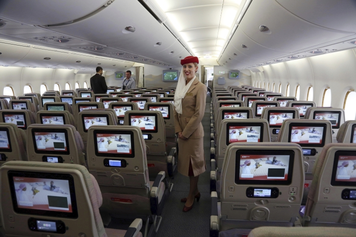 FILE - In this March 12, 2014 file photo, a stewardess stands inside an Emirates A380 aircraft, the world's largest passenger airline, during the fourth Indian Aviation show at Begumpet airport in Hyderabad, India. Emirates airline said in a statement Thursday, Jan. 18, 2018, that they are purchasing 20 A380 aircraft with the option for 16 more in a deal worth $16 billion, throwing a lifeline to the European-made double-decker jumbo jets. (AP Photo/Mahesh Kumar A., File)