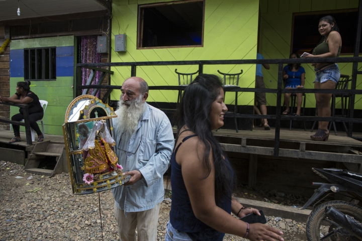 In this Jan. 10, 2018 photo, Father Pablo Zabala, better known as Padre Pablo, walks to the Barrio Chino bar to return a statue of Our Lady of Forgetfulness, Triumph and Mercy, adopted by the local sex workers as their patron saint, in Boca Colorado, part of Peru's Madre de Dios region in the Amazon. The 70-year-old Spanish priest volunteered to clean the religious statue. (AP Photo/Rodrigo Abd)
