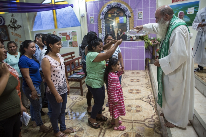 In this Jan. 14, 2018 photo, Father Pablo Zabala, better known as Padre Pablo, squirts holy water from a recycled water bottle during his last Mass as the parish priest in Boca Colorado, part of Peru's Madre de Dios region in the Amazon. After 10 years of service the 70-year-old Spanish priest has been transferred 130 kms (80 miles) away to Puerto Maldonado, known as the gateway to the Amazon jungle. (AP Photo/Rodrigo Abd)