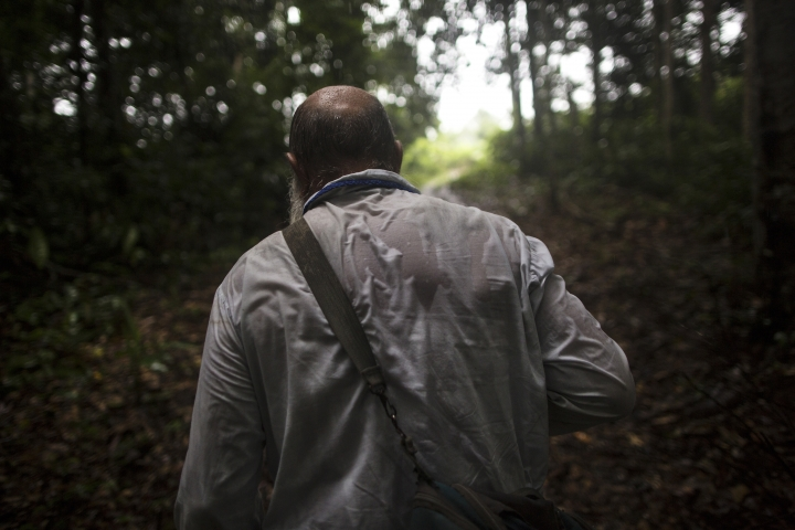 In this Jan. 15, 2018 photo, Father Pablo Zabala, better known as Padre Pablo, makes his way through the jungle under a heavy rain to the rural home of a parishioner in Boca Colorado, part of Peru's Madre de Dios region in the Amazon. More than half of Peru lies within the Amazon biome, which spans nine countries and is home to one-tenth of the world's species. (AP Photo/Rodrigo Abd)