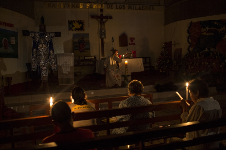 In this Jan. 8, 2018 photo, Father Pablo Zabala, better known as Padre Pablo, celebrates Mass illuminated by candlelight at a church in Boca Colorado, part of Peru's Madre de Dios region in the Amazon. The town was experiencing a power outage that lasted more than 30 hours. (AP Photo/Rodrigo Abd)