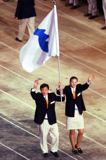 FILE - In this Sept. 15, 2000, file photo, Pak Jung Chul, left, a North Korea's Judo coach, and Chung Eun-sun, a South Korean basketball player, carry a flag representing a united Korea into Olympic Stadium during the Opening Ceremony of the Olympics in Sydney. When athletes of the rival Koreas walked together behind a single flag for the first time since their 1945 division at the start of the Sydney Olympics, it was a highly emotional event that came on the wave of reconciliation mood following their leaders' first-ever summit talks. Eighteen years later, now, the Koreas are pushing to produce a similar drama during the upcoming Pyeongchang Olympics. But they haven't generated as much enthusiastic supports as they had both at home and abroad. (AP Photo/Rusty Kennedy, File)