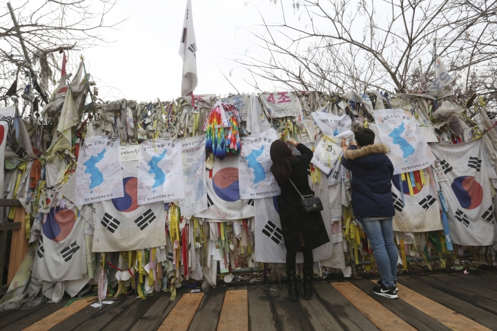 Visitors hang ribbons and unification flags wishing for reunification of the two Koreas on a border wire fence at the Imjingak Pavilion in Paju, near the border with North Korea, South Korea, Thursday, Jan. 18, 2018. (AP Photo/Ahn Young-joon)