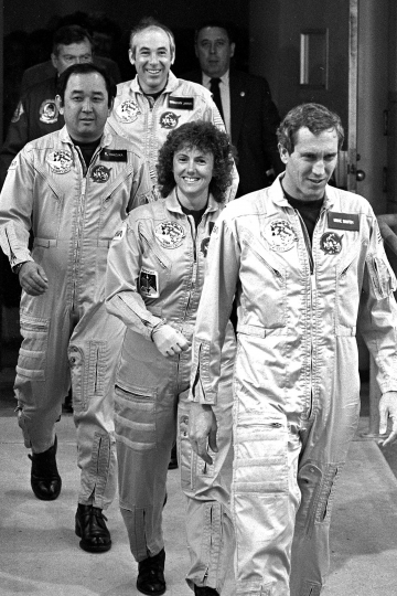 FILE - In this Jan. 28, 1986 file photo, four crew members of the space shuttle Challenger walk from their quarters at Kennedy Space Center in Floirda, en route to the launch pad. From foreground are pilot Mike Smith, school teacher Christa McAuliffe, mission specialist Ellison Onizuka and payload specialist Gregory Jarvis. Thirty-two years after the Challenger disaster, a pair of teachers turned astronauts on the International Space Station will pay tribute to McAuliffe by carrying out her science classes. (AP Photo/Steve Helber)