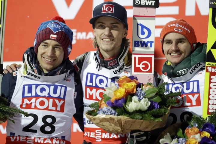 Gold medal winner Daniel Andre Tande of Norway, center, celebrates on the podium flanked by second placed Kamil Stoch of Poland, left, and third placed Richard Freitag of Germany after the Ski Flying World Championships in Oberstdorf, Germany, Saturday, Jan. 20, 2018. (AP Photo/Matthias Schrader)