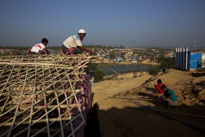 In this Friday, Jan. 19, 2018, photo, a Rohingya father and son makes their temporary shelter at Kutupalong refugee centre, near Cox's Bazar, Bangladesh. With the first repatriations of Rohingya refugees back to Myanmar just days away, and more than 1 million living in refugee camps in Bangladesh, international aid workers, local officials and the refugees say preparations have barely begun and most refugees would rather contend with the squalor of the camps than the dangers they could face if they return home. It's unclear if more than a handful of Rohingya will even be willing to go home. (AP Photo/Manish Swarup)