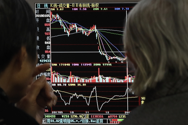 People monitor stock prices at a brokerage house in Beijing, Monday, Jan. 22, 2018. Asian stock markets were mixed Monday after global investors shrugged off the latest U.S. government shutdown. (AP Photo/Andy Wong)