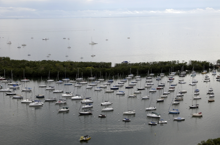 In this Tuesday, Jan. 16, 2018 photo, boats are moored at the Coconut Grove Sailing Club in the Coconut Grove neighborhood of Miami. The oasis that is Coconut Grove is just a few miles from downtown, along the shore of Biscayne Bay, with tree canopies shading the streets and historic structures scattered throughout. (AP Photo/Lynne Sladky)