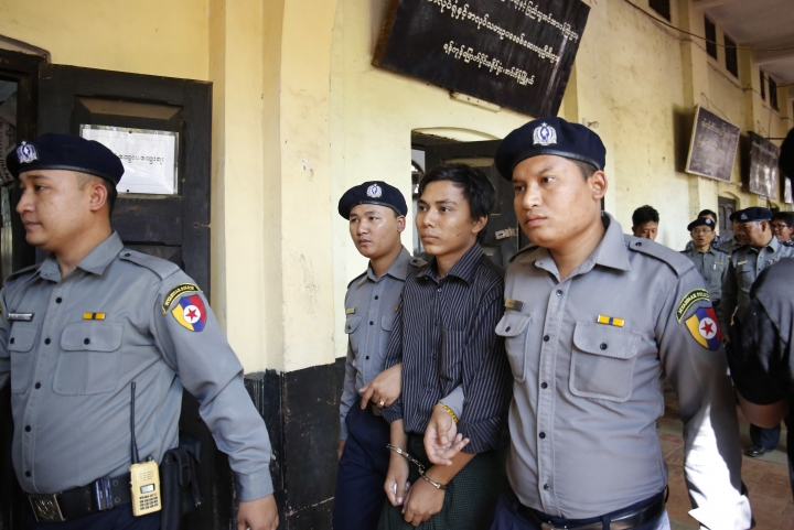 Myanmar police officers escort detained Reuters journalist Kyaw Soe Oo, center, from a court after a hearing in Yangon, Myanmar, Tuesday, Jan. 23, 2018. Two detained Reuters journalists appeared in court after being officially charged with violating Myanmar's Official Secrets Act. (AP Photo/Lamin Tun)