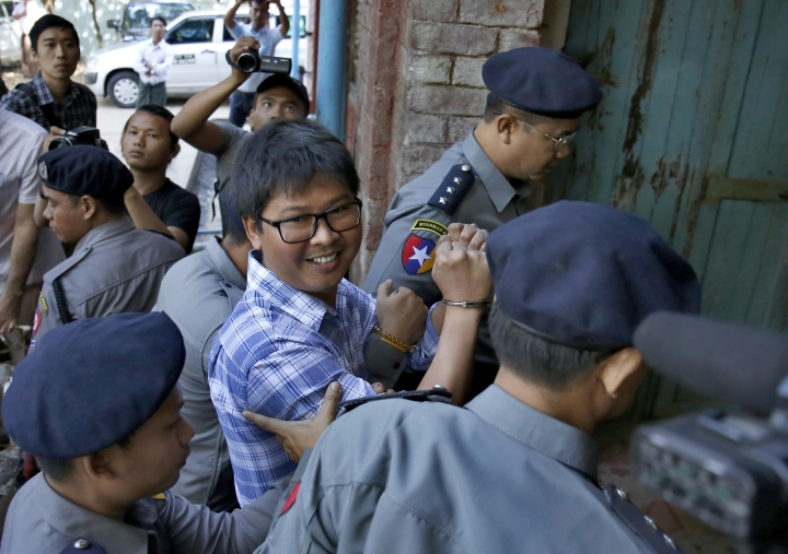 Myanmar police officers lead detained Reuters journalist Wa Lone to a court hearing in Yangon, Myanmar, Tuesday, Jan. 23, 2018. Two detained Reuters journalists appeared at a district court as their second hearing due on Tuesday after the pair was officially charged for violating the state's secrets act earlier this month. (AP Photo/Lamin Tun)