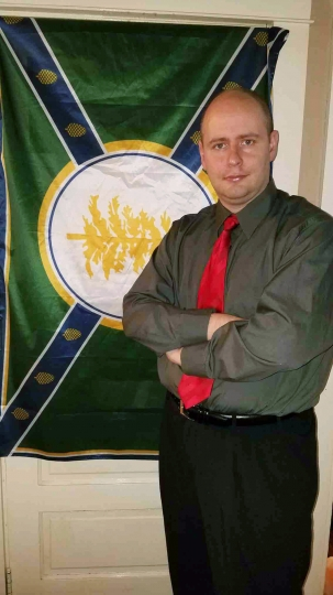 This Jan. 23, 2018 photo provided by Tom Kawczynski shows the former Jackman, Maine town manager with the flag of New Albion, a white separatist group he leads. Kawczynski was fired from his job on Tuesday, Jan. 23, 2018. Kawczynski has made comments bashing Islam and called for the preservation of white European heritage in northern New England. (Courtesy Tom Kawczynski via AP)