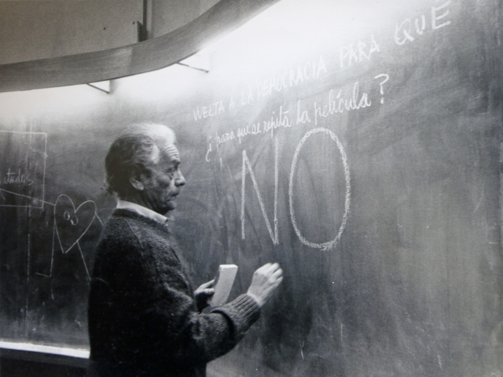 "In this 1992 photo, Nicanor Parra writes on the blackboard as he teaches a class at an engineering school in Santiago, Chile. His messages reads in Spanish ""Back to democracy for what. So the movie repeats itself? No."" Parra, a Chilean physicist, mathematician and self-described ""anti-poet"" whose eccentric writings won him a leading place in Latin American literature, died Tuesday, Jan. 23, 2018. He was 103. (AP Photo/Alvaro Hoppe)"