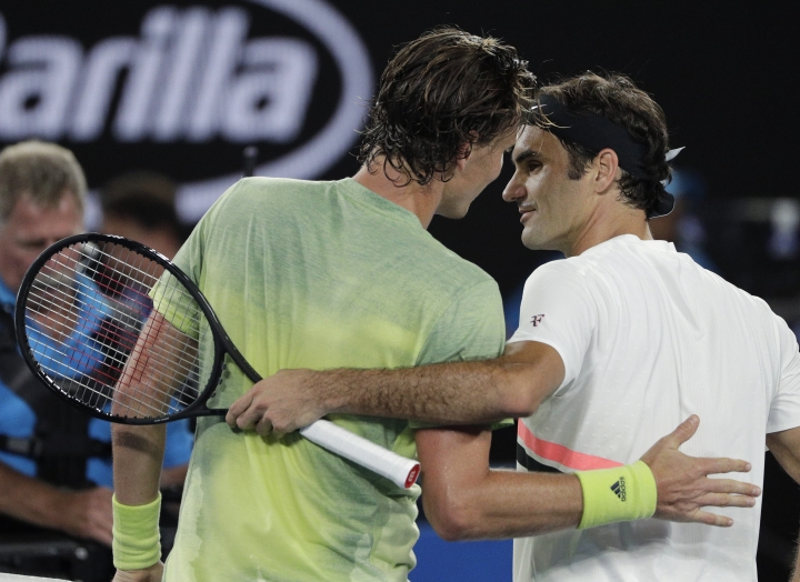 Switzerland's Roger Federer, right, is celebrated by Tomas Berdych of the Czech Republic after he won their quarterfinal at the Australian Open tennis championships in Melbourne, Australia, Wednesday, Jan. 24, 2018. (AP Photo/Dita Alangkara)