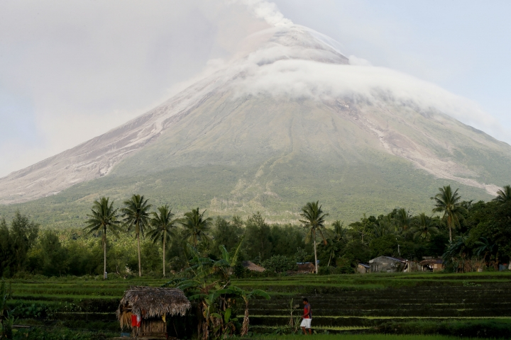 A resident walks back to his hut as Mayon volcano exhibits a lull in its eruption as seen from Legazpi city, Albay province, around 340 kilometers (200 miles) southeast of Manila, Philippines, Wednesday, Jan. 24, 2018. Lava fountaining regularly from the Philippines' most active volcano has flowed up to 3 kilometers (1.86 miles) from the crater in a dazzling but increasingly dangerous eruption. Mount Mayon has spewed lava up to 600 meters (2,000 feet) high at times Tuesday and early Wednesday and its ash plumes stretched up to 5 kilometers (3 miles) above the crater. (AP Photo/Bullit Marquez)