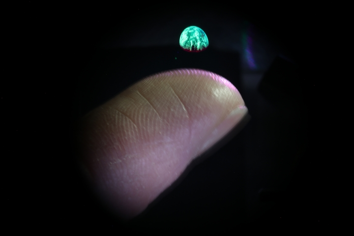 This photo provided by the Dan Smalley Lab at Brigham Young University in January 2018 shows a projected image of the earth above a finger tip in Provo, Utah. Scientists have figured out how to manipulate tiny nearly unseen specks in the air and use them to produce images more realistic than most holograms, according to a study published on Wednesday, Jan. 23, 2018, in the journal Nature. (Dan Smalley Lab, Brigham Young University via AP)