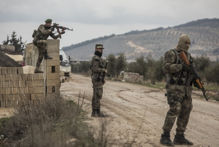 "Turkey-backed Free Syrian Army fighters secure an area where Turkish army's Operation Olive Branch continue in Azaz, northwestern Syria, Wednesday, Jan. 24, 2018. Turkish President Recep Tayyip Erdogan says Turkey's incursion into a Kurdish-held enclave in Syria is progressing ""successfully"" and will continue until the last ""terrorist"" is eliminated. (DHA-Depo Photos via AP)"