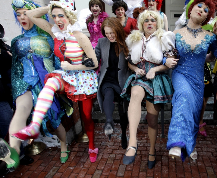 FILE - In this Jan. 27, 2011 file photo, actress Julianne Moore, center, named Harvard University's Hasty Pudding Theatricals woman of the year, dances in a kickline with male cast members dressed as women, on the steps of the New College Theatre in Cambridge, Mass. As the theater group prepares to honor its 2018 winners, critics have called for the troupe to start casting women in its burlesque musical productions and to update stage portrayals of women that some say are sexist. The group has had an all-male cast for more than 170 years. (AP Photo/Stephan Savoia, File)