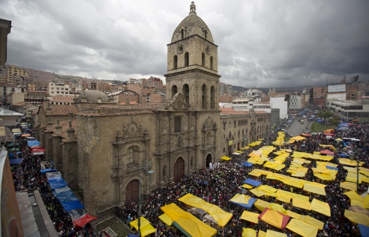 Vendors of miniature items fill the street outside San Francisco Basilica on the first day of the annual Alasita fair in downtown La Paz, Bolivia, Wednesday, Jan. 24, 2018. Thousands people attended the opening day of the fair to buy tiny replicas of things they aspire to acquire during the year, like homes, cars, wealth and love. (AP Photo/Juan Karita)