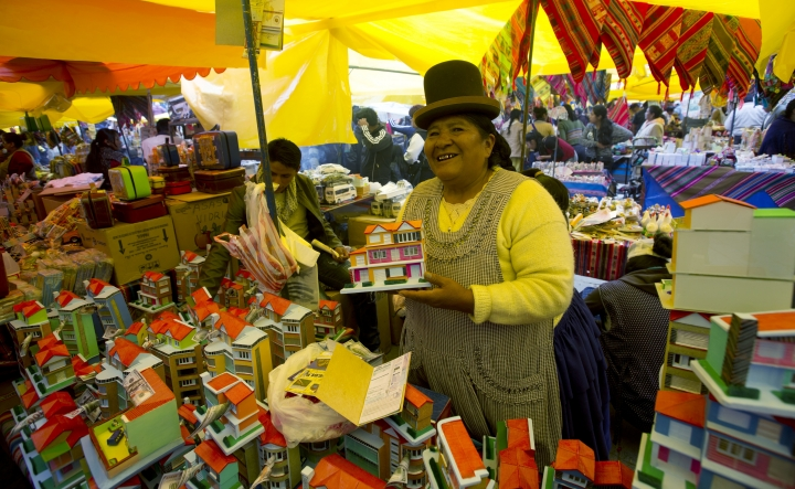 Vendor Maria Luisa sells miniatures homes at the annual Alasita fair in downtown La Paz, Bolivia, Wednesday, Jan. 24. 2018. Thousands people attended the opening day of the fair to buy tiny replicas of things they aspire to acquire during the year, like homes, cars, wealth and love. (AP Photo/Juan Karita)