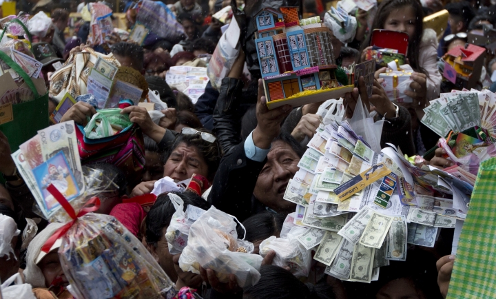 People hold up miniature homes and fake money for a blessing by a Catholic priest outside San Francisco Basilica on the opening day of the Alasita fair in downtown La Paz, Bolivia, Wednesday, Jan. 24. 2018. Thousands people attended the annual fair to buy tiny replicas of things they aspire to acquire during the year, like homes, cars, wealth and love. (AP Photo/Juan Karita)