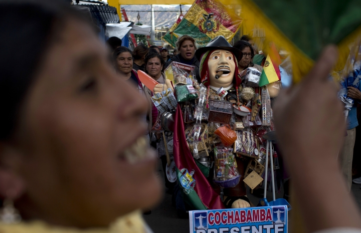 People accompany the statue of Ekeko, the Bolivian god of prosperity and the central figure of the Alasita miniature fair, in La Paz, Bolivia, Tuesday, Jan. 23, 2018. The United Nations Educational, Scientific and Cultural Organization, UNESCO, declared the fair of Alasita intangible heritage of humanity on Dec. 2017. (AP Photo/Juan Karita)