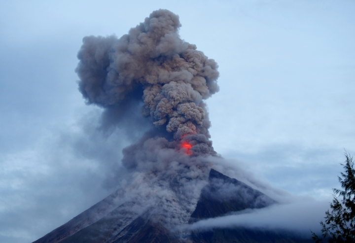 Mayon volcano spews molten lava during its sporadic eruption early Thursday, Jan. 25, 2018 as seen from a village in Legazpi city, Albay province, around 340 kilometers (200 miles) southeast of Manila, Philippines. The Philippine Institute of Volcanology and Seismology said the volcano that's been erupting for almost two weeks still appears to be swelling with magma under the surface. More than 74,000 people are staying in dozens of emergency shelters as Mount Mayon continues to belch lava, ash and superheated gas and rocks. (AP Photo/Bullit Marquez)