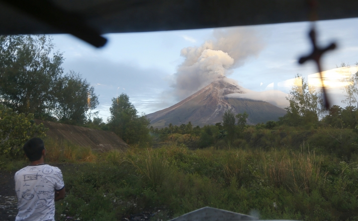 A public transport driver looks at an erupting Mayon volcano early Thursday, Jan. 25, 2018 as seen from a village in Legazpi city, Albay province, around 340 kilometers (200 miles) southeast of Manila, Philippines. The Philippine Institute of Volcanology and Seismology said the volcano that's been erupting for almost two weeks still appears to be swelling with magma under the surface. More than 74,000 people are staying in dozens of emergency shelters as Mount Mayon continues to belch lava, ash and superheated gas and rocks. (AP Photo/Bullit Marquez)