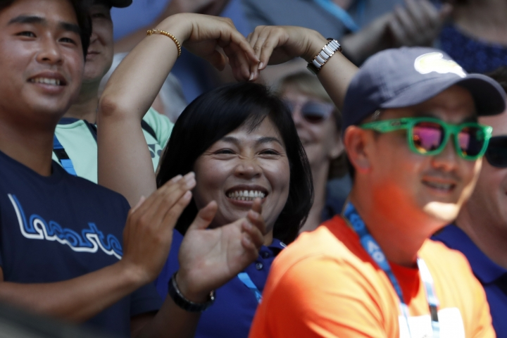 Kim Young-mi, mother of South Korea's Chung Hyeon makes a sign for love as she cheers for her son after his win over United States' Tennys Sandgren in their quarterfinal at the Australian Open tennis championships in Melbourne, Australia, Wednesday, Jan. 24, 2018. (AP Photo/Ng Han Guan)