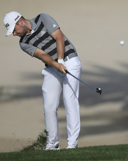 England's Chris Hatton plays a shot on the 14th hole during the first round of the Dubai Desert Classic golf tournament in Dubai, United Arab Emirates, Thursday, Jan. 25, 2018. (AP Photo/Kamran Jebreili)