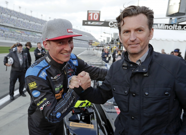 Renger Van Der Zande, left, of the Netherlands, gets a handshake from former racing driver and TV automotive racing host Justin Bell, after qualifying for the pole position in the IMSA 24-hour auto race at Daytona International Speedway, Thursday, Jan. 25, 2018, in Daytona Beach, Fla. (AP Photo/John Raoux)